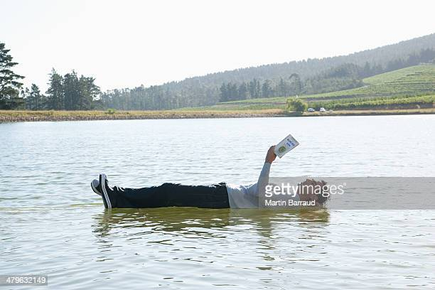 Man lying down on water reading book