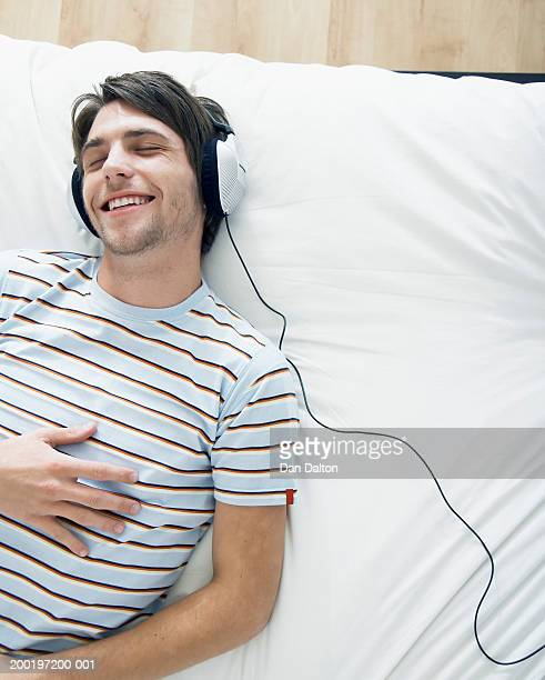 Man lying down wearing headphones, smiling, eyes closed, elevated view