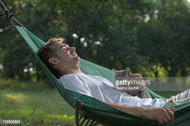 a man lying in a hammock petting a cat - one animal stock pictures, royalty-free photos & images