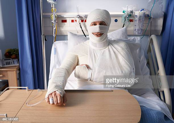 man lying in a hospital bed, covered in bandages - bandage stock photos and pictures