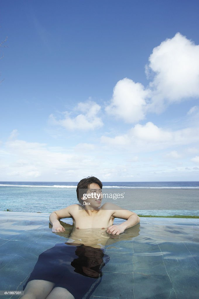 Man Lying in a Swimming Pool : Stock Photo