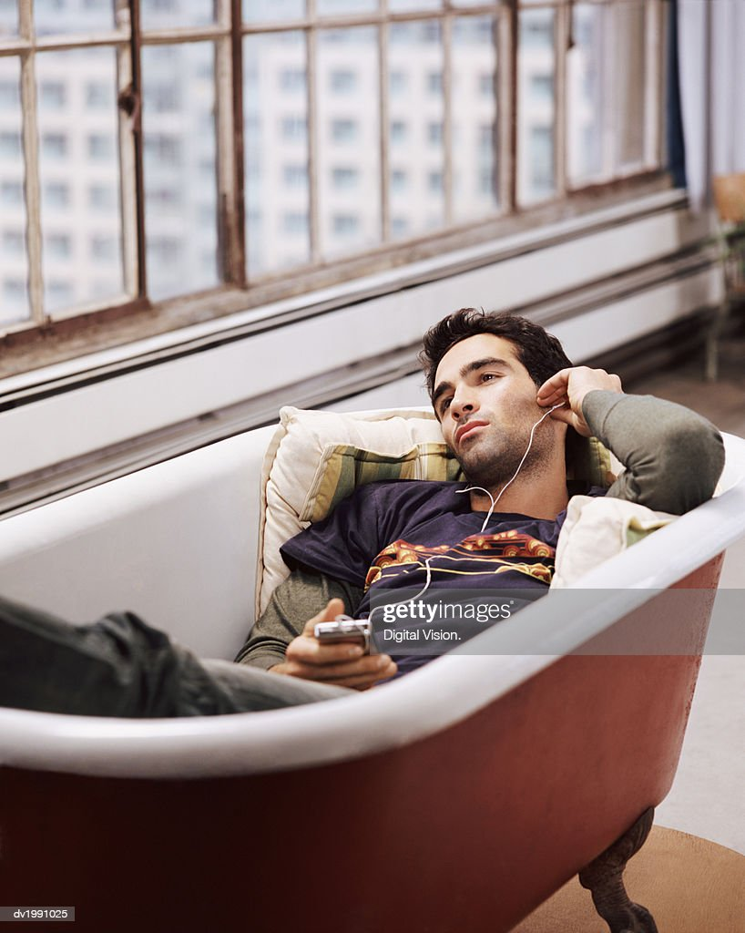 Man Lying in an Empty Bath Listening to Music on an MP3 Player : Stock Photo