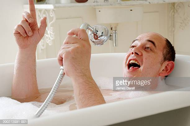 Man lying in bath singing into shower head, close-up