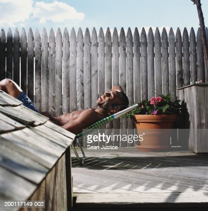Man Lying In Beach Chair On Roof Deck Wearing Headphones Side View Stock Photo Getty Images
