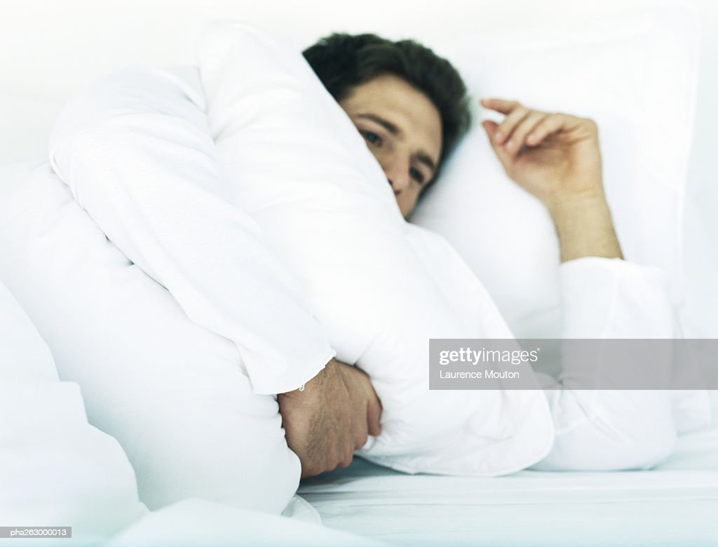 Man lying in bed on side holding pillow : Stockfoto