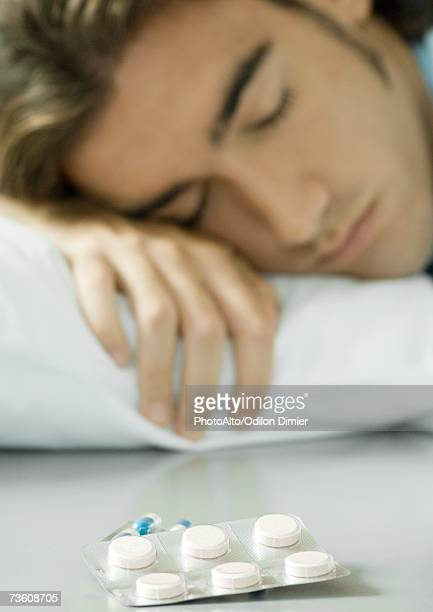 Man lying in bed, pack of pills in foreground