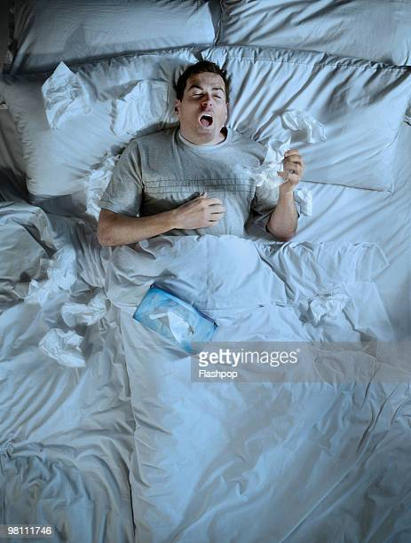 man lying in bed sneezing into a tissue - cold and flu stock pictures, royalty-free photos & images