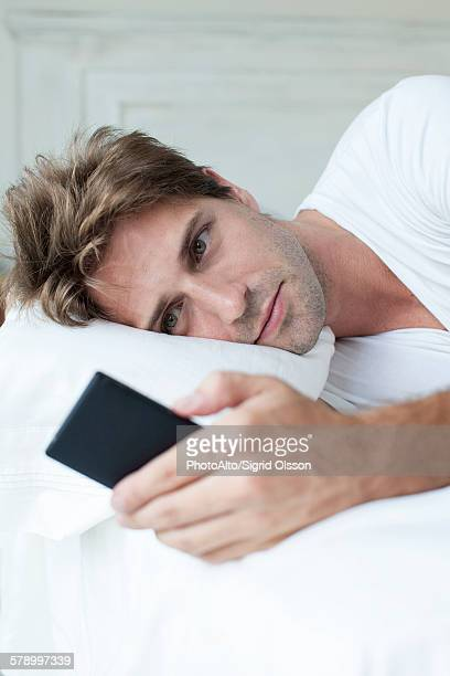 Man lying in bed using smartphone