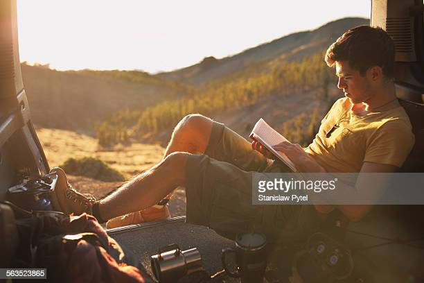 Man lying in car, reading book, on journey