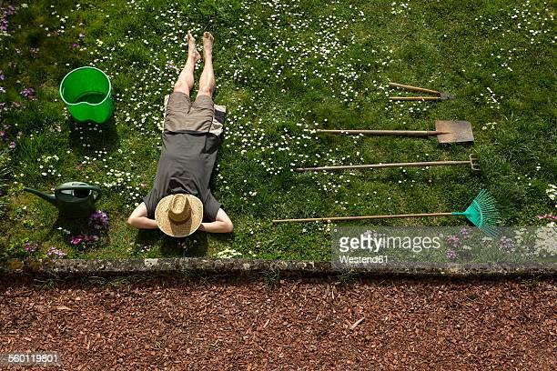 Man lying in grass relaxing from gardening