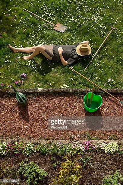 Man lying in grass relaxing from gardening