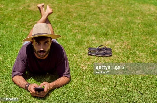 man lying in grass using his smartphone - 麦わら帽子 ストックフォトと画像