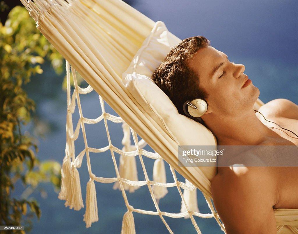 Man Lying in Hammock Listening to Headphones : Stock Photo