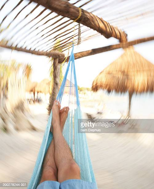 man lying in hammock on beach - legs crossed at ankle stock pictures, royalty-free photos & images