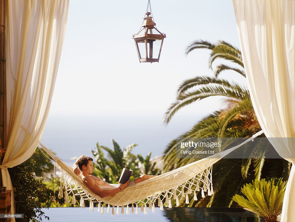 Man Lying in Hammock Reading a Book : Stock Photo