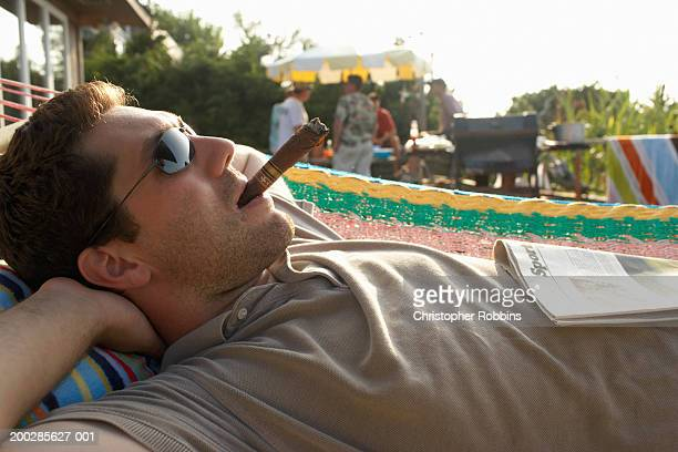 Man lying in hammock smoking cigar, friends by barbecue in background