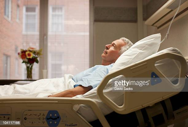 man lying in hospital bed - patience stock pictures, royalty-free photos & images