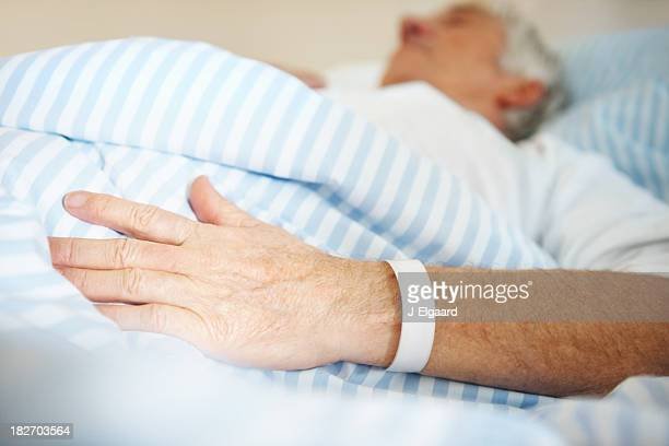 Man lying in hospital bed with a band on hand