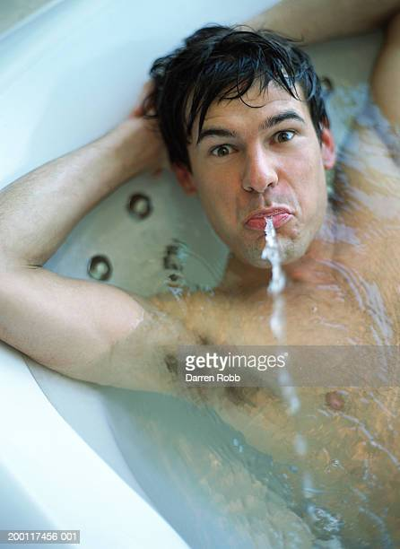 Man lying in hot tub spitting water, hands behind head, portrait