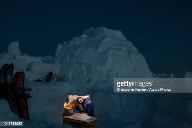 man lying in igloo - igloo stock pictures, royalty-free photos & images