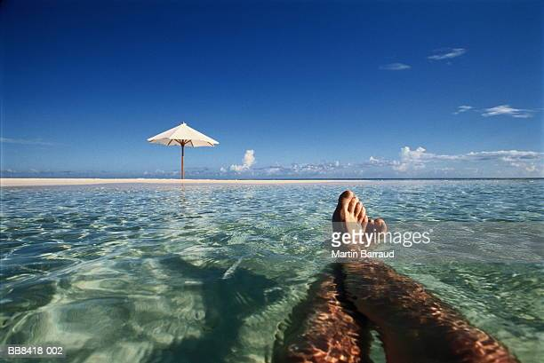 Man lying in sea, view over legs to parasol on beach, Maldives