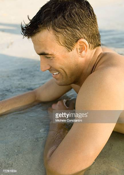 Man lying in shallow water
