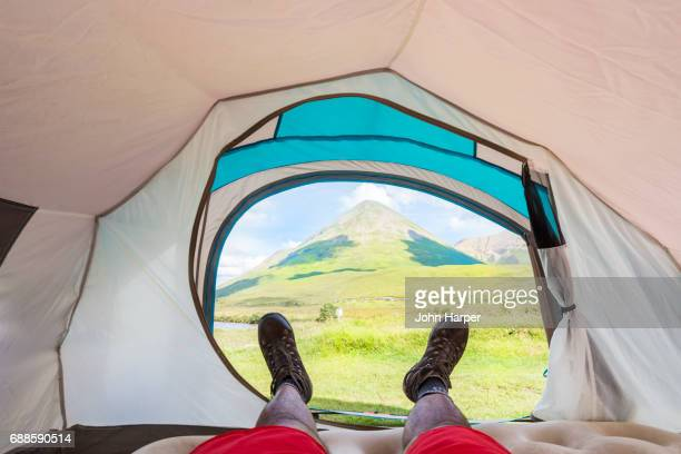 POV of man lying in tent viewing mountain, Scottish Highlands.