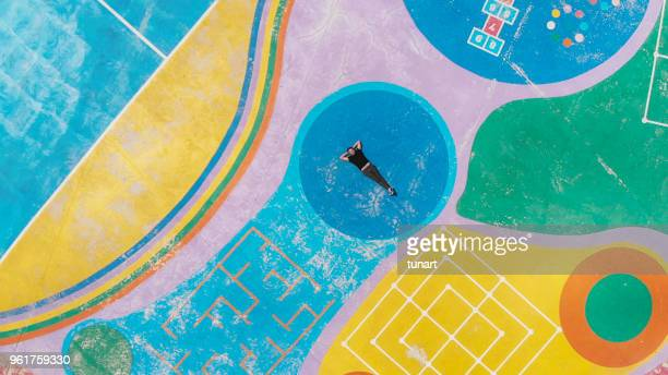 man lying in the middle of a colorful playground and remembering his childhood - hopscotch stock pictures, royalty-free photos & images