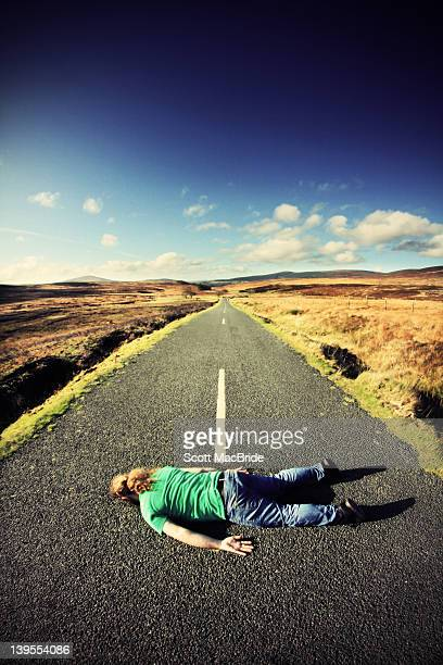man lying middle of road - scott macbride stock pictures, royalty-free photos & images