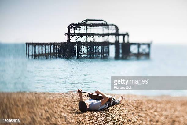 A man lying on a beach with a guitar
