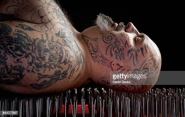 man lying on a bed of nails. - faquir - fotografias e filmes do acervo
