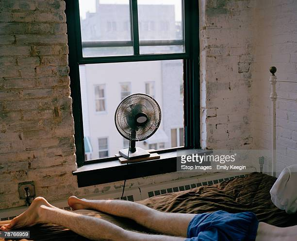 A man lying on a bed with a fan blowing
