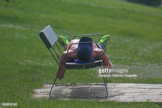 man lying on a bench in a park on a hot day