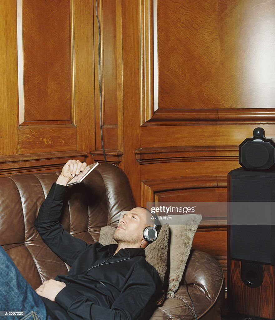 Man Lying on a Leather Sofa Listening to Music on Headphones and Looking at a Compact Disk Case : Stock Photo
