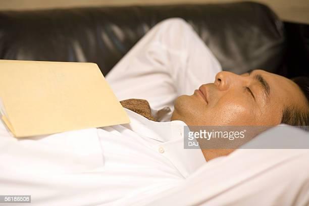 Man lying on a leather sofa