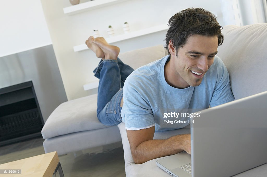 Man Lying on a Sofa in a Living Room Using a Laptop Computer : Stock Photo