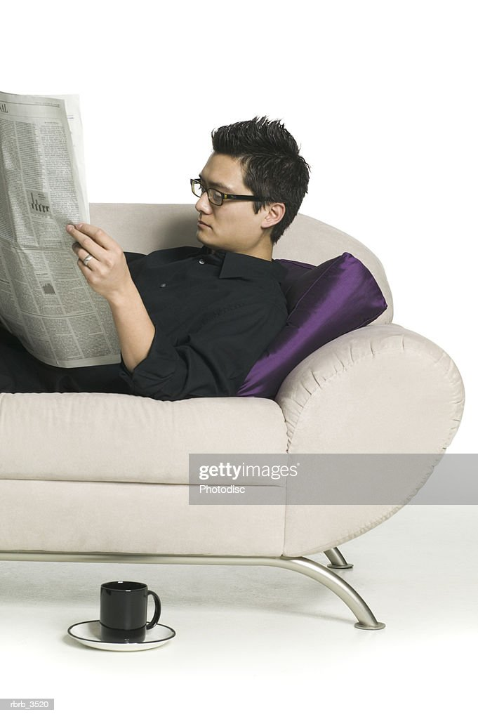 Man lying on a sofa reading a newspaper : Foto de stock