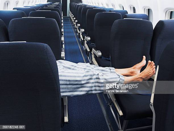 Man lying on aeroplane seats, legs stretched across aisle, low section
