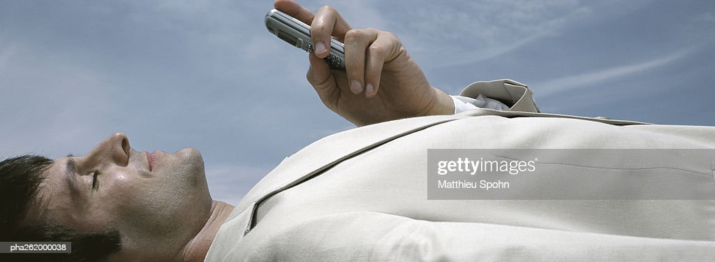 Man lying on back holding cell phone with sky in background, close-up : Stock Photo