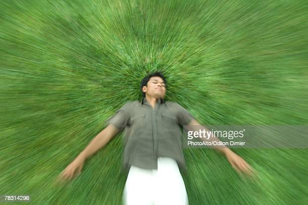 Man lying on back in grass with eyes closed, blurred motion