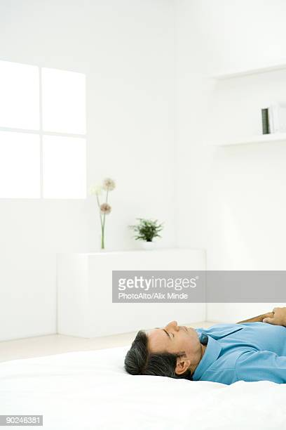 Man lying on back on bed, eyes closed