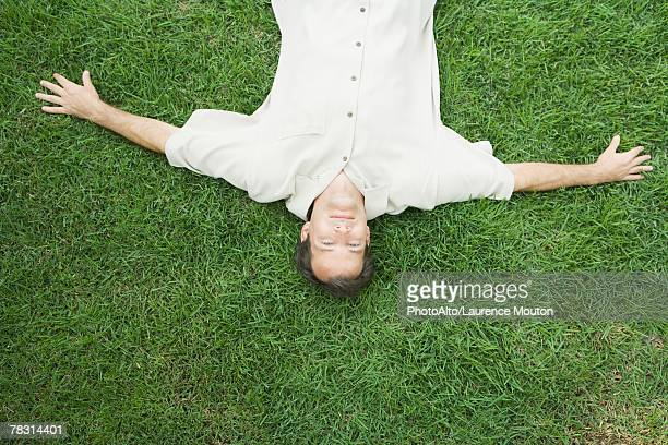 man lying on back on grass, smiling at camera, viewed from directly above - liegen stock-fotos und bilder