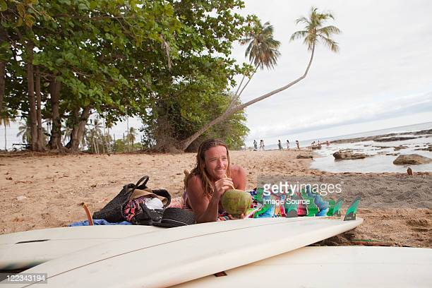 Man lying on beach drinking coconut milk