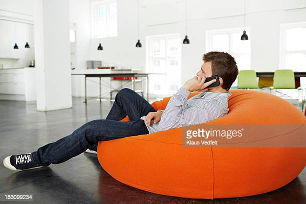 man lying on beanbag talking on smartphone - sacco photos et images de collection