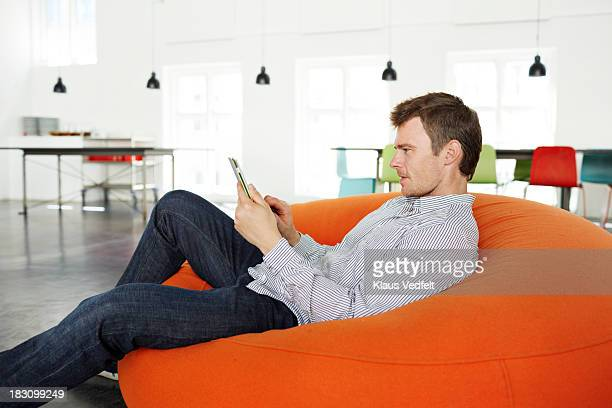 man lying on beanbag with tablet