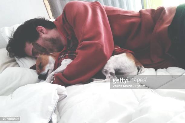 man lying on bed at home with dog - weekend activities stock pictures, royalty-free photos & images