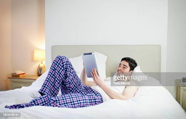man lying on bed looking at digital tablet