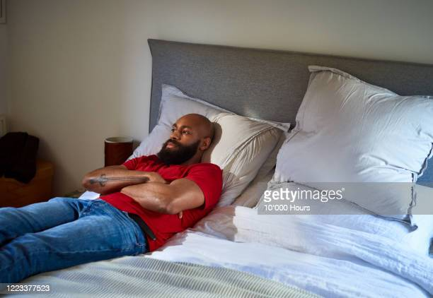 man lying on bed thinking - boredom stock pictures, royalty-free photos & images