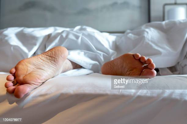 man lying on bed under the quilt - resting stock pictures, royalty-free photos & images
