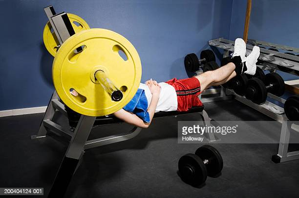 man lying on bench press, face obscured by wheel - obscured face stock pictures, royalty-free photos & images